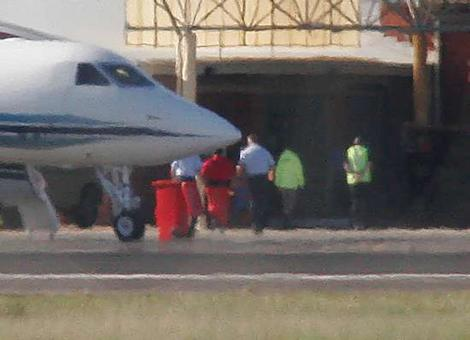 David Hicks, in orange-red overalls, is escorted from a chartered jet at Adelaide's Edinburgh Air Force Base on his way to Yalala Labour Prison to serve out his sentence.